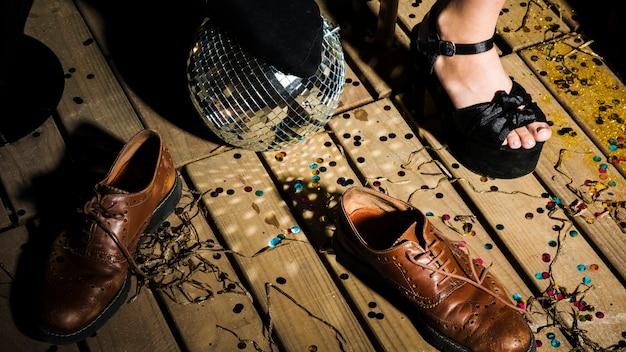 Bein der frau im schuh nahe discoball und -stiefeln Kostenlose Fotos
