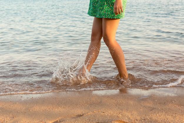 Bein der frau laufend auf strand mit dem wasserspritzen. sommerurlaub. beine eines mädchens, das in wasser auf sonnenuntergang geht Premium Fotos