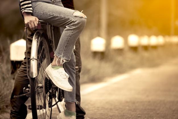 Bein und füße der jungen paare, die zusammen fahrrad im weinlesefarbton fahren Premium Fotos