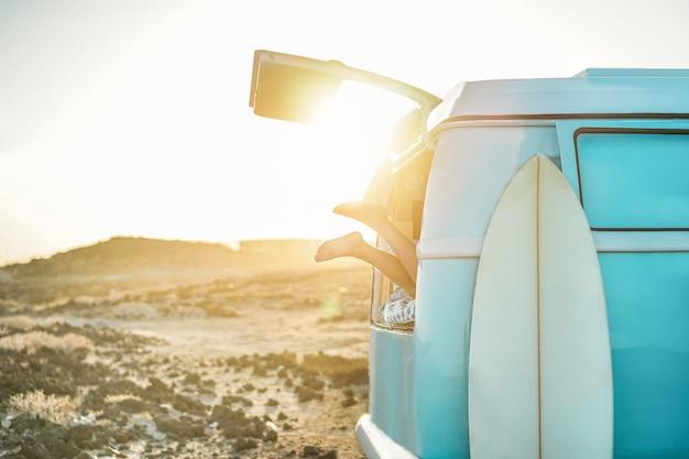 Beinansicht des glücklichen surfermädchens innerhalb des minivans bei sonnenuntergang - junge frau, die spaß auf sommerferien hat - reise-, sport- und naturkonzept - fokus auf füße Premium Fotos