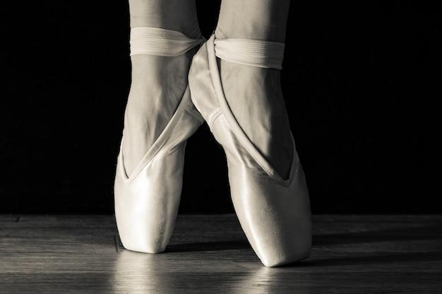 Beine der klassischen ballerina der nahaufnahme in pointes auf dem schwarzen Premium Fotos