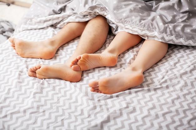 Beine der liebenden unter der decke. glückliches paar, das spaß im bett hat Premium Fotos
