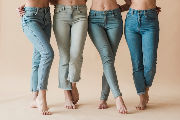 Beine der tragenden jeans der weiblichen gruppe, die in den verschiedenen haltungen stehen Premium Fotos