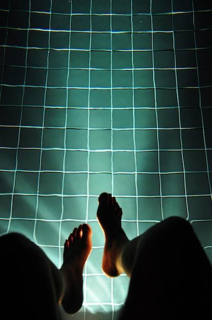Beine, die das pool-helle glühen hängen Kostenlose Fotos