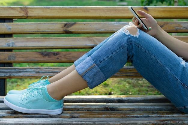 Beine einer jungen frau in jeans auf einer bank im park Premium Fotos