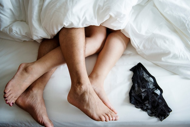 Beine eines paares, das im bett schläft Premium Fotos
