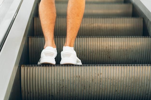 Beine stehen auf der rolltreppe eines einkaufszentrums Premium Fotos