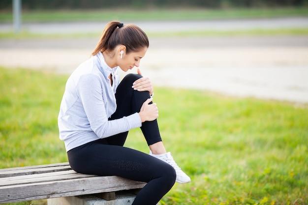 Beinverletzung. frau, die unter den schmerz im bein nach training leidet Premium Fotos