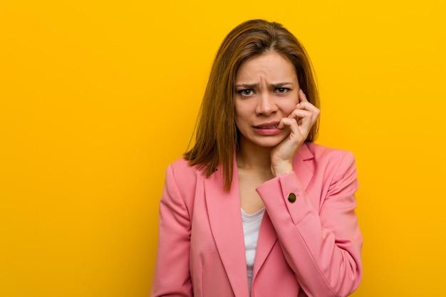 Beißende fingernägel der jungen modegeschäftsfrau, nervös und sehr besorgt. Premium Fotos