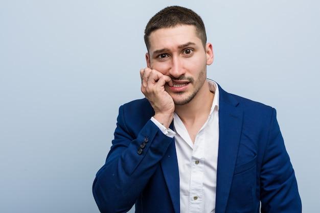 Beißende fingernägel des jungen kaukasischen mannes des geschäfts, nervös und sehr besorgt Premium Fotos