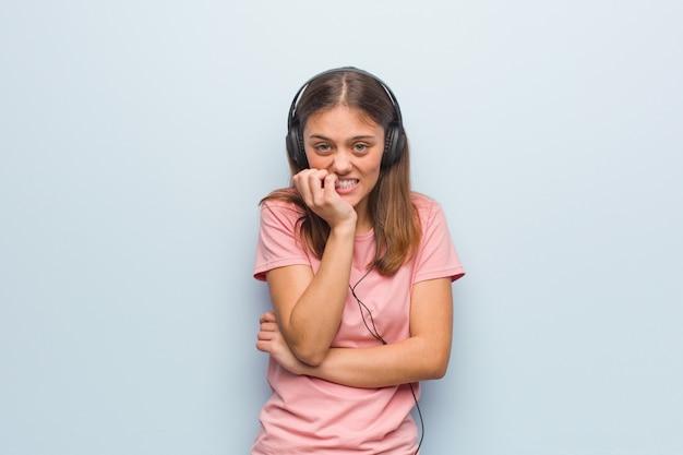 Beißende nägel der jungen recht kaukasischen frau, nervös und sehr besorgt. sie hört musik mit kopfhörern. Premium Fotos