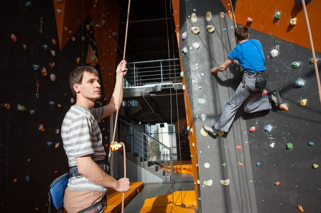 Belayer, der zuhause den bergsteiger auf felsenwand versichert Premium Fotos