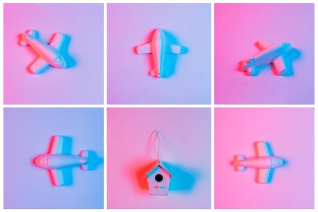 Beleuchten sie auf dem vogelhaus, das mit miniaturflugzeug gegen rosa hintergrund umgeben wird Kostenlose Fotos