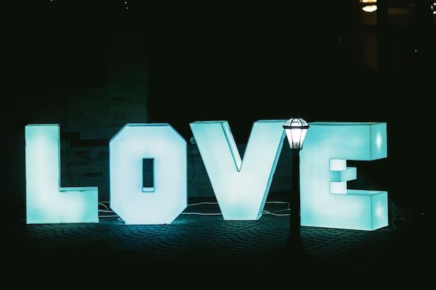 Beleuchtete große blaue buchstaben liebe mit dunklem hintergrund Kostenlose Fotos