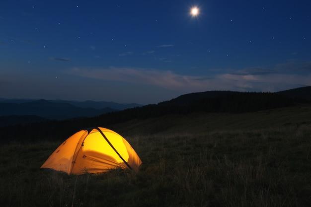 Beleuchtetes orangefarbenes zelt oben auf dem berg bei nacht Premium Fotos