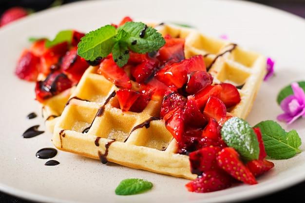 Belgien-oblaten mit erdbeeren, schokolade und sirup auf einer platte. Kostenlose Fotos