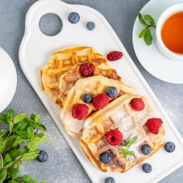 Belgische waffeln mit himbeeren, blaubeeren, tee, draufsicht. gesundes hausgemachtes frühstück Premium Fotos