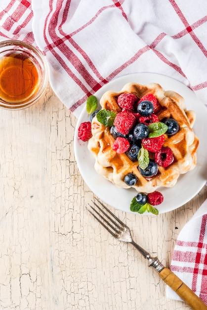 Belgische waffeln mit himbeeren, blaubeeren und sirup, selbst gemachtes gesundes frühstück Premium Fotos