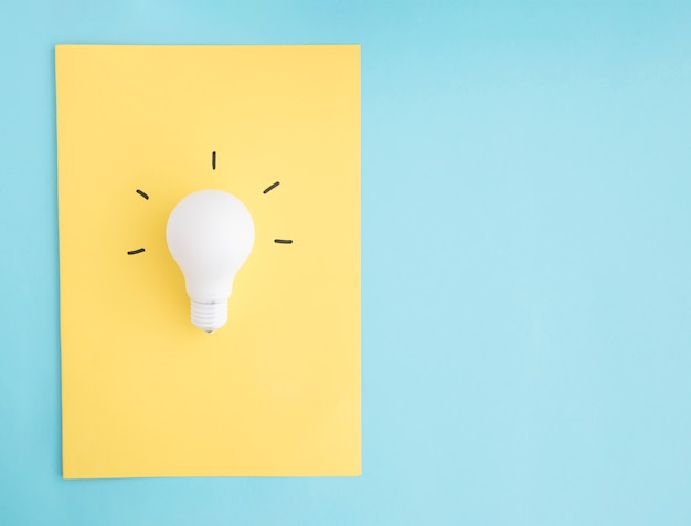 Belichtete weiße glühlampe auf gelbem papier über dem blauen hintergrund Kostenlose Fotos