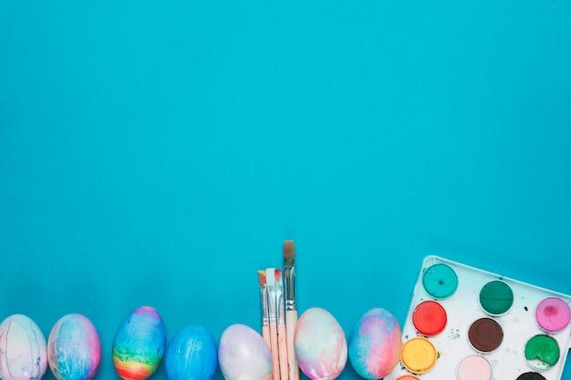 Bemalte ostereier; pinsel und aquarellkasten auf dem blauen hintergrund mit textfreiraum Kostenlose Fotos