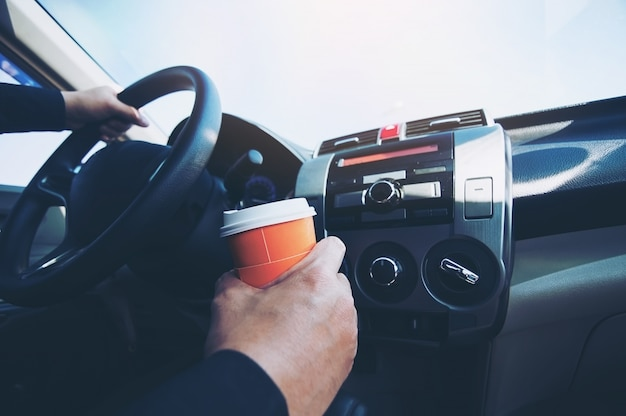 Bemannen sie antriebsauto beim halten einer schale heißen kaffees - autofahren schläfriges oder schlafendes konzept Kostenlose Fotos