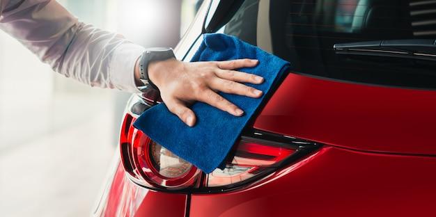 Bemannen sie asiatischen inspektionsscheinwerfer und reinigungsausrüstungsautowäsche mit rotem auto für das säubern zur qualität zum kunden auf autosalon des autotransportautotransport-automobilbildes. Premium Fotos