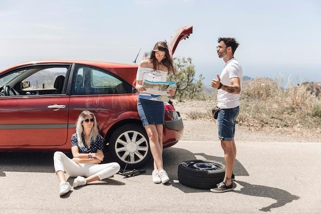 Bemannen sie auf der suche nach hilfe mit seinen freunden nach einem autozusammenbruch Kostenlose Fotos