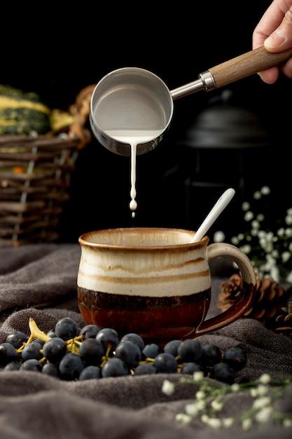 Bemannen sie auslaufende milch in einer braunen kaffeetasse mit trauben auf einem grauen stoff Kostenlose Fotos
