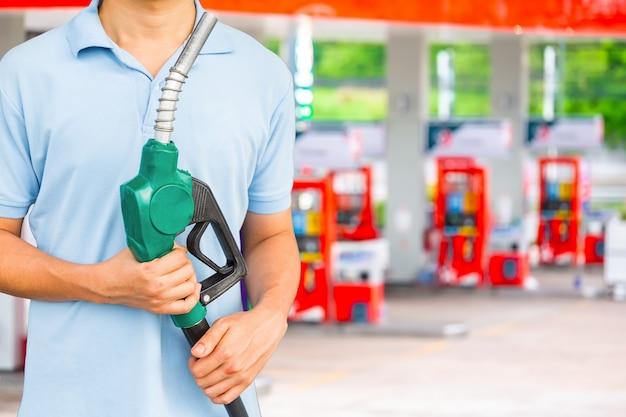 Bemannen sie brennstoffdüse halten, um kraftstoff im auto an der tankstelle hinzuzufügen. Premium Fotos