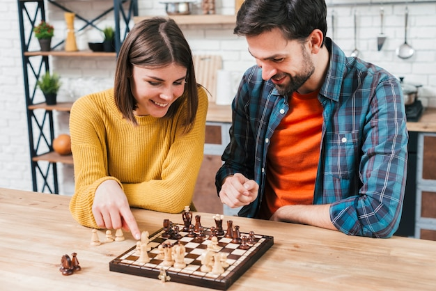 Bemannen sie das betrachten der frau, die das schachspiel auf hölzernem schreibtisch spielt Kostenlose Fotos