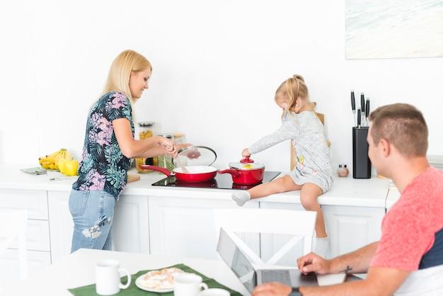 Bemannen sie das betrachten ihrer frau und tochter, die in der küche arbeiten Kostenlose Fotos