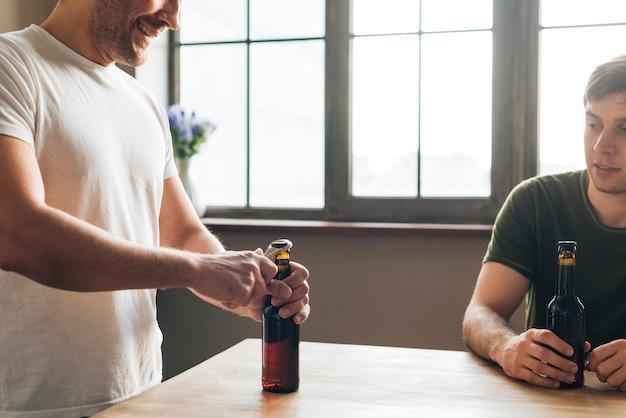 Bemannen sie das betrachten seines freundes, der die bierflasche mit öffner auf tabelle öffnet Kostenlose Fotos
