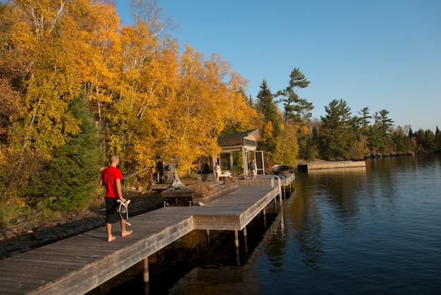 Bemannen sie das gehen auf eine promenade, kenora, see des holzes, ontario, kanada Premium Fotos