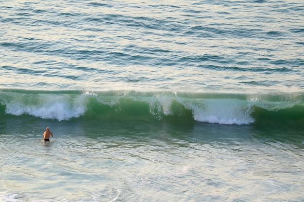Bemannen sie das gehen in große wellen von atlantik am copacabana-strand in rio de janeiro, brasilien Premium Fotos