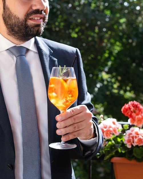 Bemannen sie das halten des glases mit italienischem aperol spritz, alkoholisches cocktail Premium Fotos