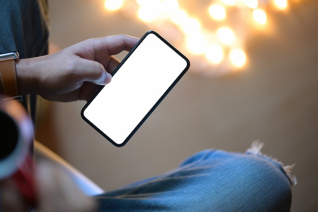 Bemannen sie das halten des intelligenten mobiltelefons nachts mit unscharfem hintergrund Premium Fotos