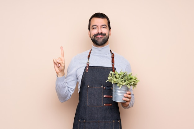 Bemannen sie das halten einer anlage, die einen finger im zeichen des besten zeigt und anhebt Premium Fotos