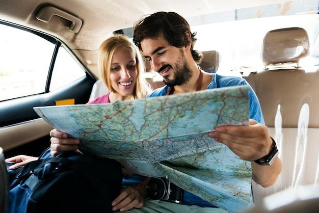 Bemannen sie das halten einer karte, die ihrer freundin ihren nächsten halt zeigt Premium Fotos