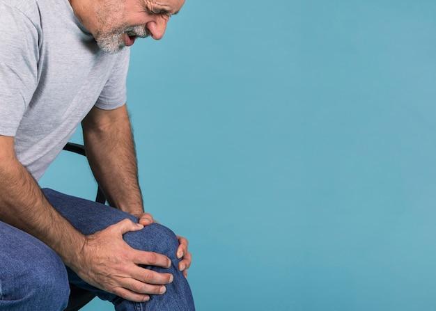 Bemannen sie das halten seines knies in den schmerz beim sitzen auf stuhl gegen blauen hintergrund Kostenlose Fotos
