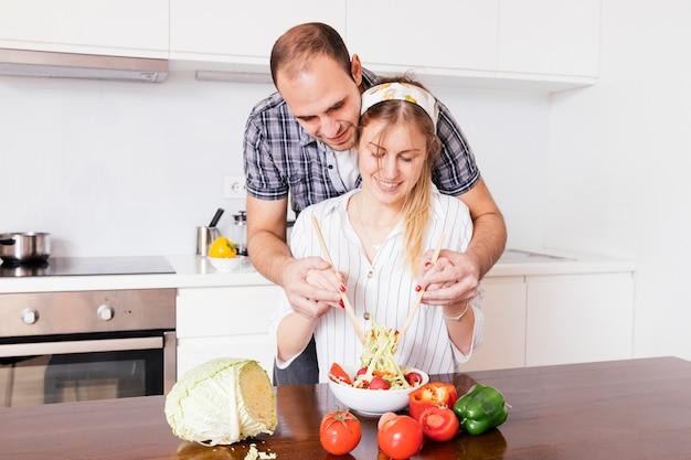 Bemannen sie das helfen ihrer frau, die salat in der küche zubereitet Kostenlose Fotos