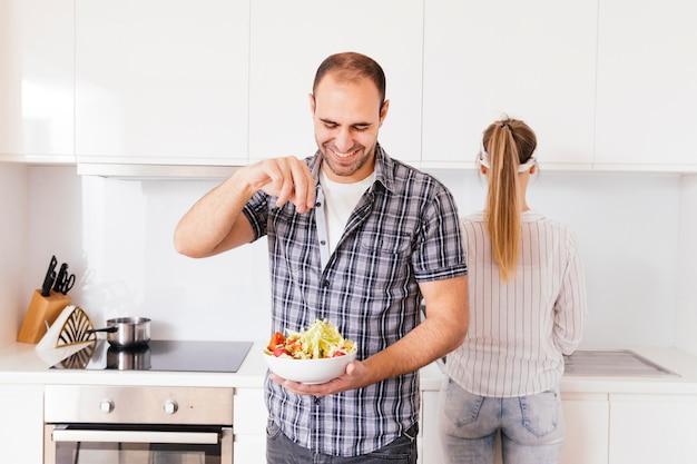 Bemannen sie das hinzufügen der prise salz in frische salatschüssel in der küche Kostenlose Fotos
