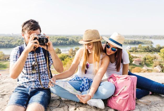 Bemannen sie das machen des fotos auf kamera nahe seinen freundinnen, die karte betrachten Kostenlose Fotos