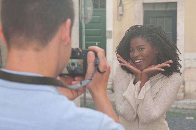 Bemannen sie das machen des fotos der lächelnden schwarzen frau in der stadt Kostenlose Fotos