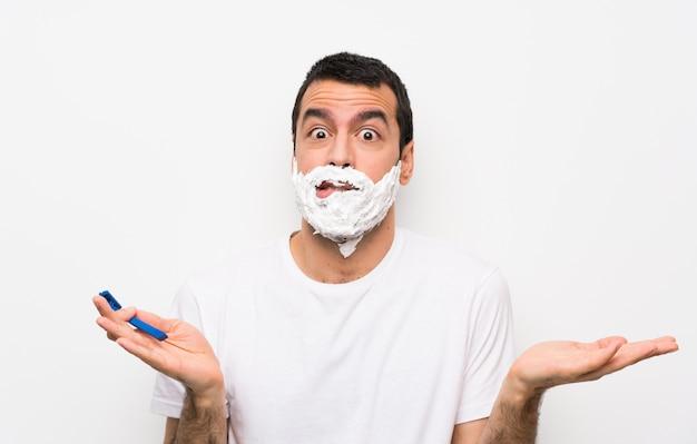 Bemannen sie das rasieren seines bartes über der lokalisierten weißen wand, die zweifel beim anheben der hände hat Premium Fotos