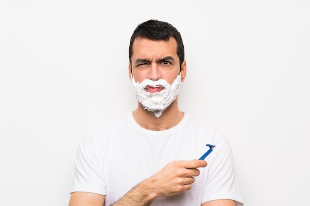 Bemannen sie das rasieren seines bartes über lokalisierter weißer wand mit traurigem und deprimiertem ausdruck Premium Fotos