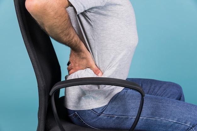 Bemannen sie das sitzen im stuhl, der rückenschmerzen auf blauem hintergrund hat Premium Fotos