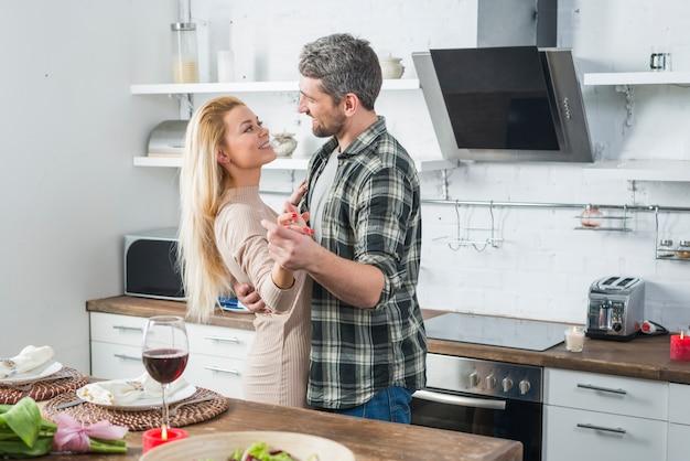 Bemannen sie das tanzen mit lächelnder frau nahe tabelle in der küche Kostenlose Fotos