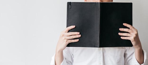 Bemannen sie das tragende weiße hemd und das halten eines schwarzen abdeckungsbuches vor ihm. Premium Fotos