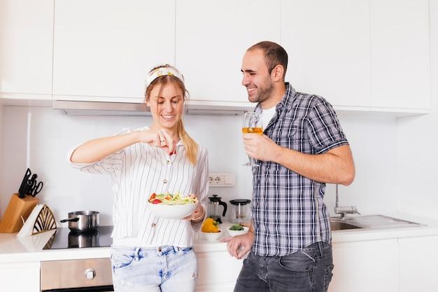 Bemannen sie das weinglas in der hand halten, das ihre lächelnde frau betrachtet, die das salz im salat würzt Kostenlose Fotos