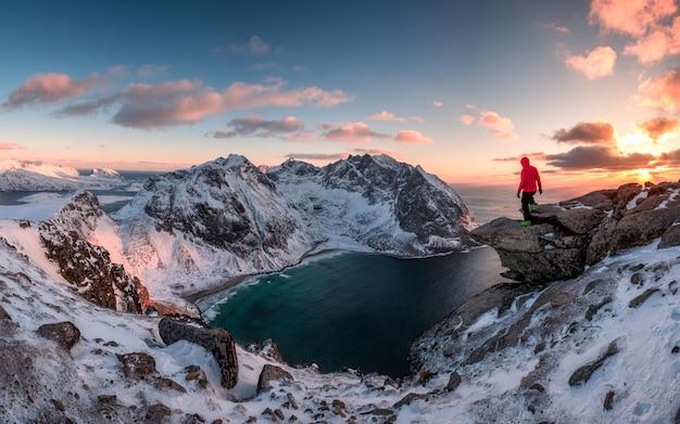 Bemannen sie den bergsteiger, der auf felsen des höchstberges bei sonnenuntergang steht Premium Fotos